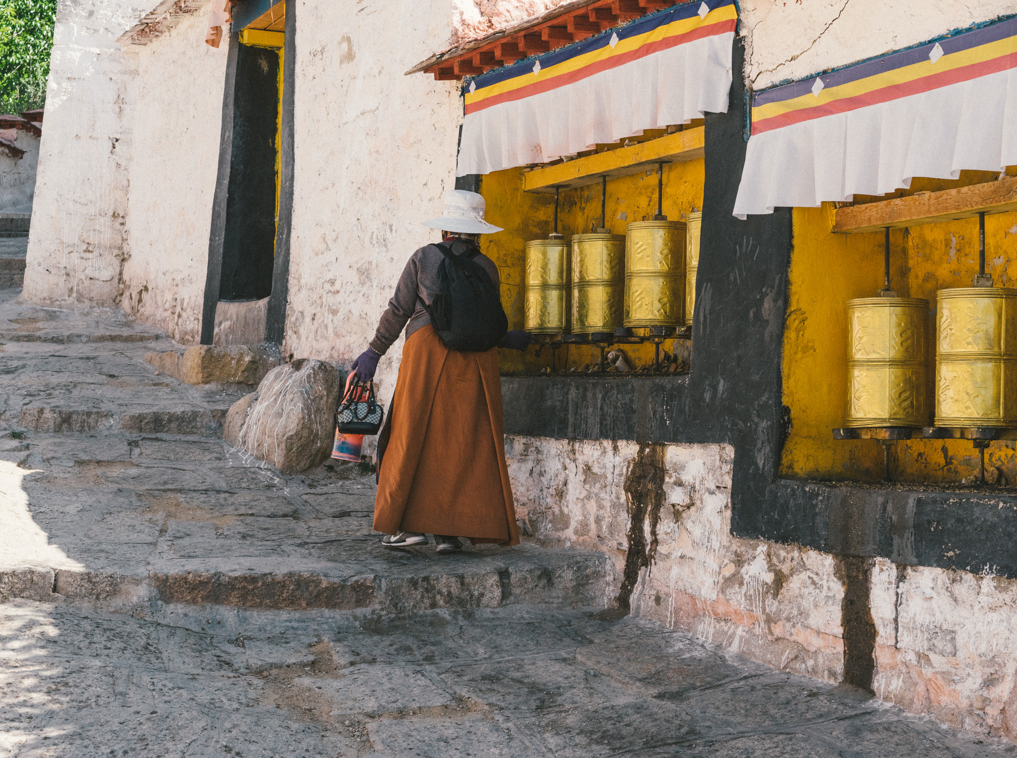 Tibetan woman spinning prayer wheels in the Sera Monastery