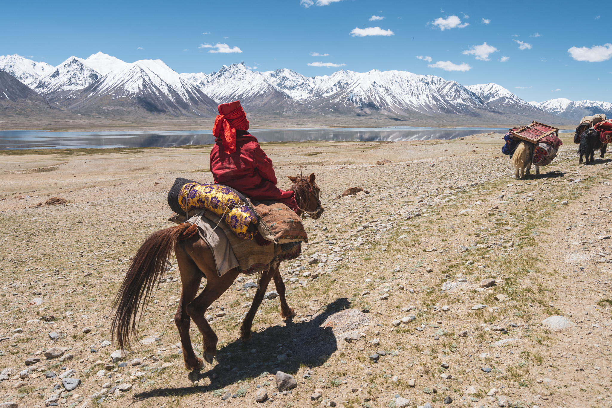Kyrgyz girl rides her horse in the Little Pamir, with lake Chaqmaqtin in the distance